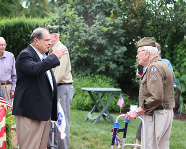 Zelienople mayor Thomas Oliverio salutes World War II veteran Donald Wunnenberg, 93, during the finale for the Zelienople Historical Society's Patriotic Porch Tour week celebration. Festivities included honoring veterans, a single-engine plane flyover, historic figure reinactors and other events. Seb Foltz/Butler Eagle 07/08/21