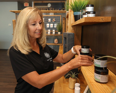 Beth Durban adjusts a display at My CBD Store in Moraine Point Plaza Wednesday. Seb Foltz/Butler Eagle 07/07/21