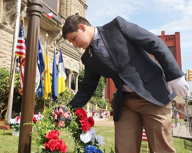 Collin Klee, 10, places a wreath at the base of the new Revolutionary War anniversary memorial at the Butler County Courthouse during Saturday's unveiling ceremony Saturday. Seb Foltz/Butler Eagle