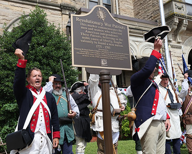 Revolutionary War reenactors from the Captain William Trent Company and German Regiment celebrate the unveiling of the patriots marker during Saturday's Daughters of the American Revolution memorial dedication ceremony at the Butler County Courthouse. Seb Foltz/Butler Eagle 07/10/21