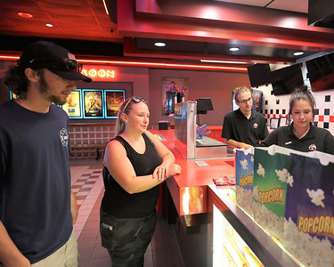 Cydnei Neff, 17, and Bobby Thompson, 17, wait for their tickets Friday at Moraine Point Cinema. Friday was the theater's soft opening in what was formerly a Regal Cinema-owned theater. Seb Foltz/Butler Eagle 07/09/21