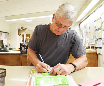Retiree Larry Neff of Oakland Twp. fills out his antlerless application in the Butler County Treasurer's office Monday morning. Harold Aughton/Butler Eagle.