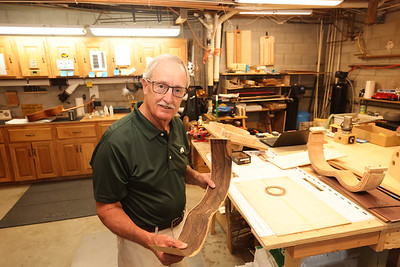 Gary Neyman shows a sample of wood vacuum molded into the shape of the side of a guitar. Seb Foltz/Butler Eagle 07/07/21