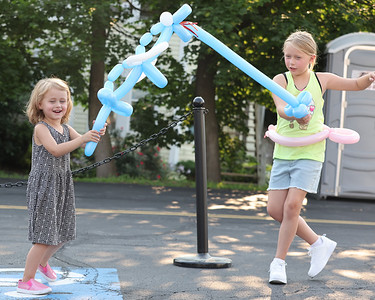 Rose Florentine, 3, (left) and her sister Lillian, 8, sword and dragon fight with their balloon animals at Thursday's Mingle on Main in Saxonburg Thursday. Seb Foltz/Butler Eagle 07/15/21