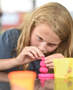 Ashley Schmeier of Butler builds a snowman out of play dough during craft time at the Grace Youth and Family Foundation summer program at Rotary Park in Butler Thursday afternoon. Harold Aughton/Butler Eagle