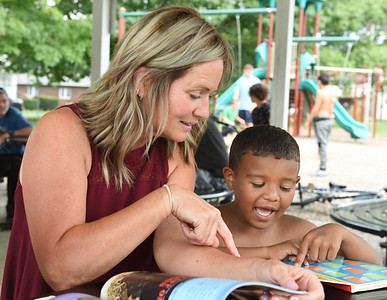 Elementary school teacher, Lee Dittman, works with Brandon Campbell to sound out words during a reading session during the Grace Youth and Family Foundation summer program at Rotary Park in Butler Thursday afternoon. Harold Aughton/Butler Eagle.