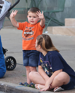 River Selfridge, 3, waves at motorcycle riders in the Butler Bikes & BBQ parade down Main St. Thursday. The weekend event, in its first year, will be held at the Butler Farm Show Grounds. Seb Foltz/Butler Eagle 07/22/21