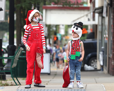 Clad for Christmas, Nevin Steele, 11, and his brother Lucas Steele, 4, wait to cross the street while handing out candy canes on Main St.  during Butler's Christmas in July Saturday. Seb Foltz/Butler Eagle 07/24/21