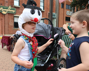 Geared for the holliday season, Lucas Steele, 4, hands out candy canes to other kids on Main St. Saturday during Butler's Christmas in July on Main St. Seb Foltz/Butler Eagle 07/24/21