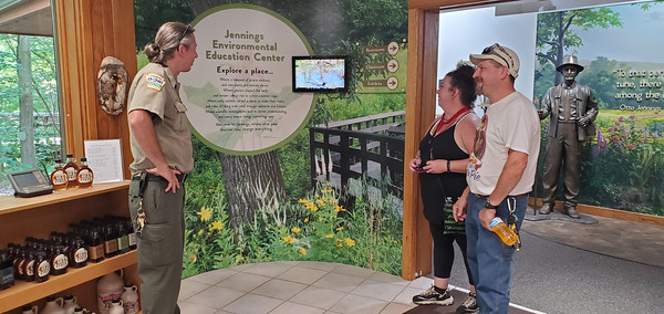 Manager Wil Taylor (left) gives visitors Becky and Greg Koller (right) some information about the Jennings Environmental Education Center following a guided tour Sunday. Nathan Bottiger/Butler Eagle