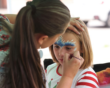 Emilia Dalton, 8, of Mars gets her face painted Saturday during Christmas in July on Main St. in Butler. Seb Foltz/Butler Eagle 07/24/21