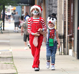 Clad for Christmas, Nevin Steele, 11, and his brother Lucas Steele, 4, hand out candy canes on Main St.  during Butler's Christmas in July Saturday. Seb Foltz/Butler Eagle 07/24/21