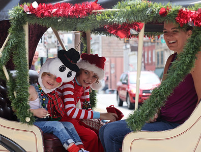 Lucas Steele, 4, (front) and his brother Nevin, 11, smile from a horse carriage with their mother Stephanie Steele at Saturday's Butler Christmas in July. Seb Foltz/Butler Eagle 07/24/21