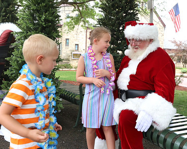 Piper Shockey, 6, and her brother Parker talk to Santa in Diamond Park Saturday during Butler's Maint St. Christmas in July. Seb Foltz/Butler Eagle 07/24/21