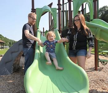Adam Fair, 32,  and his wife Paige Volek, 33, help their son Elliott Fair down the slide at Butler's Memorial Park Friday. Seb Foltz/Butler Eagle 07/23/21