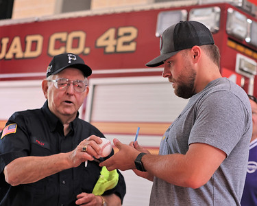 Pirate pitcher David Bednar of Mars signs an autograph for Adams Area Fire District's A.D. 'Buzz' Kelly Tuesday in Adams Township, part of a visit with first responders. Seb Foltz/Butler Eagle 07/27/21