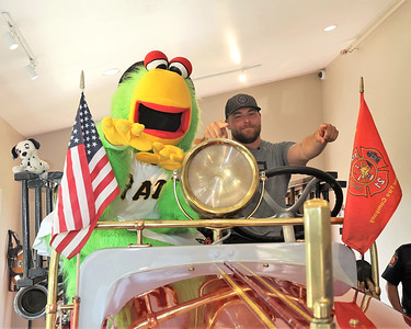 The Pirate Parrot and pitcher David Bednar pose on Cranberry Township's antique fire truck Tuesday, part of a meet-and-greet tour with area first responders. Seb Foltz/Butler Eagle 07/27/21