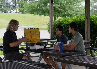 Parks are still convenient meeting places: Tom Murrin of Drone Addiction discusses Mars New Year festival plans with Patricio (18) and Santiago Beltran (14) of Mars at an Adams Township Community Park pavilion. Photo: Julia Maruca