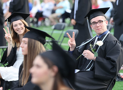 Cousins Zachary and Bridgit Tate give peace signs to family in the stands at Seneca Valley Graduation Tuesday night. Seb Foltz/Butler Eagle 2021