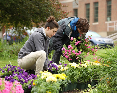 Slippery Rock High School's Riley Martin and Cullen Birkes plant flowers in Slippery Rock Memorial Park Saturday along with volunteers from the Slippery Rock Rotary's Slippery Rock in Bloom group. Seb Foltz/Butler Eagle 05/29/21