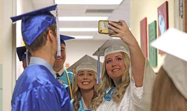 Caitlin Buchanan (right) and Drew Davis (center) pose for a selfie prior to Union High School Graduation Wednesday. Seb Foltz/Butler Eagle 06/02/21