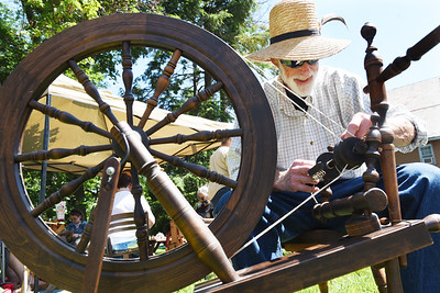 Ed Rowe sets up a Saxony Spinning Wheel to spin wool outside Weaver's Cabin in Harmony Saturday morning. Harold Aughton/Butler Eagle.