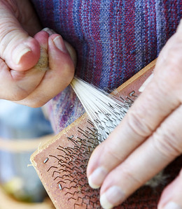 Marilyn Merbach of Saxonburg works on flicking the fleece a process that cleans and opens the fibers  prior to spinning it.