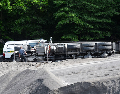 A Pennsylvania State Police officer investigates the scene of an overturned truck at Wiest Asphalt Tuesday afternoon. The truck driver was transported by Saxonburg Ambulance to the Butler Hospital where the driver was transported by a LifeFlight helicopter to a Pittsburgh hospital. Harold Aughton/Butler Eagle.