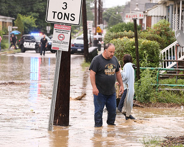 James Caldwell of Butler wades through flooding on West Brady Street, where it crosses Sullivan Run. Residents came out to try to clear debris with rakes in an attempt to mitigate flash flooding Wednesday. Seb Foltz/Butler Eagle 06/09/21