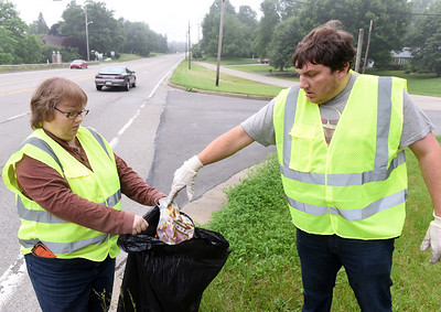 Maryann Fleeger holds a trash bag for her son, Adam Fleeger, Saturday morning along Route 8 in Center Township.  This year marks the 30th anniversary since the Lions Club took part in Pennsylvania's Adopt A Highway program. Members picked up trash along the two mile section of highway just north of the city. Other participating members included, Connie Ivill, John Hertzog and Mike Winkler. Harold Aughton/Butler Eagle