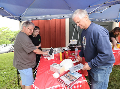 Bob Arturo of Center Township buys books and a hot dog from Kurt Rauschenberger and his daughter Rachel at Saturday's Butler County Historical Society event at the Lowrie House. Seb Foltz/Butler Eagle 06/19/21