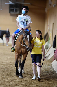 Kevin Anderson takes part in a horseback riding activity with a little help from Karlee Satterfield, a Slippery Rock University recreational therapist student, as part of Camp Rock, Monday, June 21, 2021. Harold Aughton/Butler Eagle