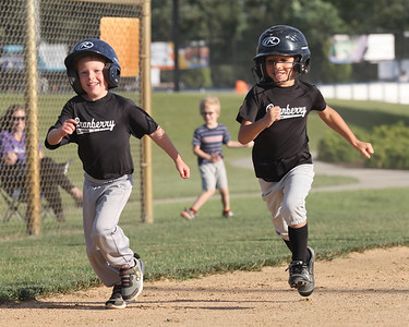 Gavin Roczko, 5,(left) and Ben Bassaly,5, round third and run home to score during the final inning of a Cranberry Township teeball game  at Graham Park Tuesday evening. Seb Foltz/Butler Eagle 06/15/21