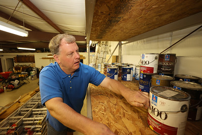 Rusty Stirling, 52, of Stirling Painting, Wallpapering, and Contracting, reaches for a paint can in the company's warehouse. Seb Foltz/Butler Eagle June 2021