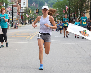 Leah Anne Weaver, 28, finishes first in the women's division of the Butler Road Race 5-mile course. Weaver also finished fifth overall. Seb Foltz/Butler Eagle 06/19/21