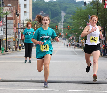 Rylee Hurley,14, finishes first in the women's division of the Butler Road Race 2 kilometer run. Seb Foltz/Butler Eagle 06/19/21