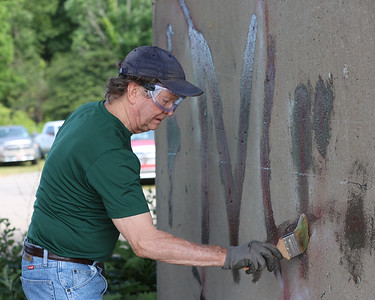 Sky Pfahl of Slippery Rock applys a paint remover to graffiti under the Route 528 bridge at Morraine State Park Saturday. Ten to 15 volunteers worked with park staff to clean the area around the 528 Boat Launch. Seb Foltz/Butler Eagle 0626/21