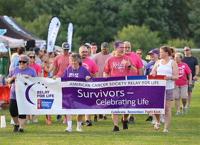Susan Grabowski (left), Joyce Fox and Alan Wolf hold the banner and lead a cancer survivors lap at Saturday's Relay For Life in Cranberry.  Seb Foltz/Butler Eagle 06/26/21