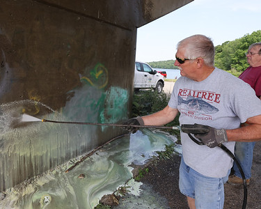 Dennis McCormick of Evans City sprays off graffiti during a volunteer park clean up day at Morraine State Park Saturday. Ten to 15 volunteers worked with park staff to apply a paint remover and clean off bridge supports at the 528 Boat Launch. Seb Foltz/Butler Eagle 06/26/21