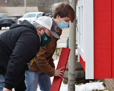 """Butler Boy Scout Troop 400 member Brady Zimmerman(right), 17, of Mars and his dad Jeff Zimmerman put the finishing touches on the new food collection """"blessing box"""" at the Middlesex Township Fire Depart. The fire department put out a request on Facebook for someone to build a food sharing box as well as a library box.  Zimmerman answered the call and made it his Eagle Scout project with the help of members of Butler Troop 400. Zimmerman designed and built two boxes, one for food and one for books, using donated materials.  Seb Foltz/Butler Eagle 02/27/20"""