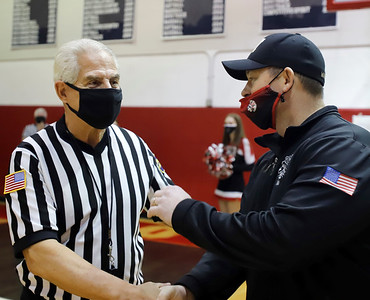 PIAA referee  Art Monteleone (left) recieves congratulations form Moniteau head football coach Robert Rottman. Monteleone was honored at Moniteau High School Saturday for his 50 serving as a basketball and football official. The district threw a surprise ceremony prior to a girls basketball game. Seb Foltz/Butler Eagle 02/20/21