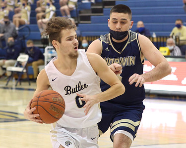Butler's Raine Gratzmiller drives to the hoop against Norwin's Nicholas Fleming in Butler's 59-46 home playoff win Tuesday. Seb Foltz/Butler Eagle 03/02/21
