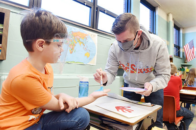 Butler Catholic first-grader Matthew Dudley takes part in an art project during Read Across America week. First-graders in Mr. Brian Herlihy's class used hand paintings to create red fish and blue fish in recognition of Dr. Seuss.  Harold Aughton/Butler Eagle.
