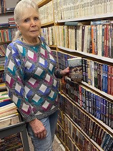 MaryAnn Shook at a shelf of western paperbacks, holding a book by William W. Johnstone. Andy Andrews/Butler Eagle