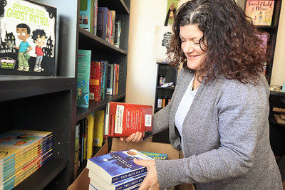 Little Green Bookstore co-owner Christine Border sorts through books in her new store on Main Street in Harmony. Border opened the store with her sister Lisa Fico. Seb Foltz/Butler Eagle 02/25/21