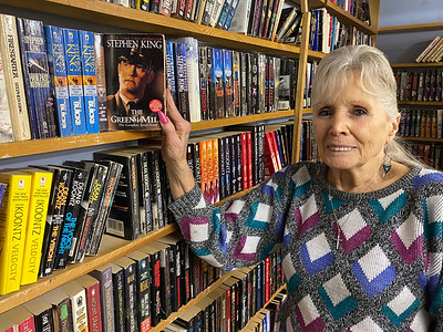 MaryAnn Shook at a shelf of horror paperbacks, holding a book by Stephen King. Andy Andrews/Butler Eagle