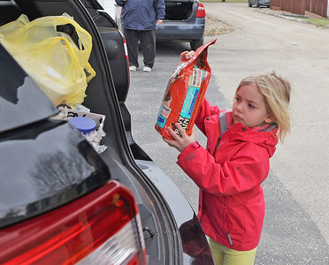 Harper Van Dorne, 4, of Harrisville lifts a bag of dog food into a police cruiser Saturday. The Harrisville Police Department hosted a Stuff the Cruiser food donation drive for the Feed My Sheep Food Cupboard in Slippery Rock. Seb Foltz/Butler Eagle 03/06/21