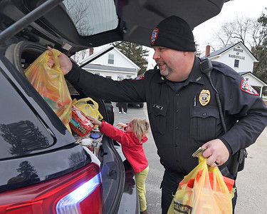 Harrisville Police Chief Alan Heller places a bags of donated food into his cruiser with Harper Van Dorne, 4. The Harrisville Police Department hosted a Stuff the Cruiser food donation drive for the Feed My Sheep Food Cupboard in Slippery Rock. Seb Foltz/Butler Eagle 03/06/21