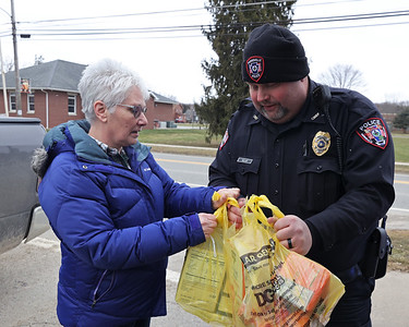 Diane Lowrey of Barkeyville hands bags of food donations to Harrisville Police Chief Alan Heller Saturday. The Harrisville Police Department hosted a Stuff the Cruiser food donation drive for the Feed My Sheep Food Cupboard in Slippery Rock. Seb Foltz/Butler Eagle 03/06/21