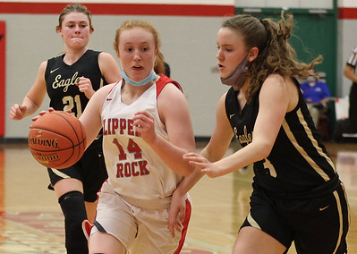 Slippery Rock's Hallie Raabe drives to the hoop against Grove City's Clara Hannon in the Rockets home playoff win Tuesday. Seb Foltz/Butler Eagle 03/10/21